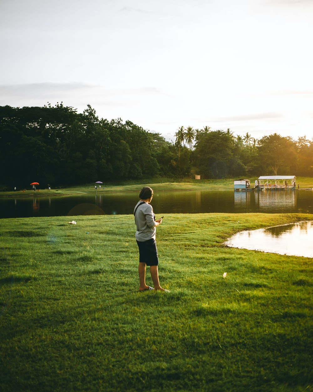 man in white t-shirt and black shorts standing on green grass field near lake during