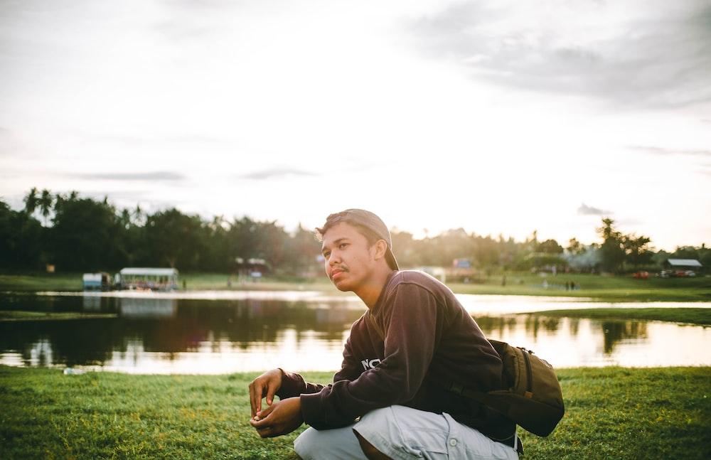 man in gray hoodie sitting on grass field near lake during daytime
