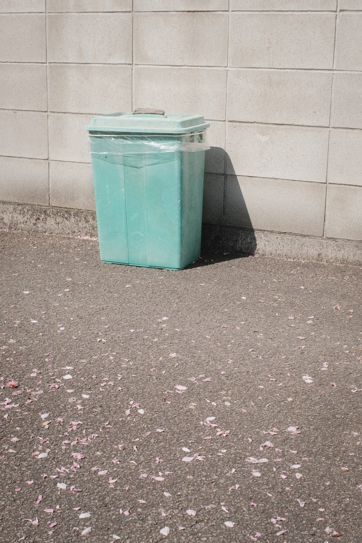 green plastic trash bin beside white wall