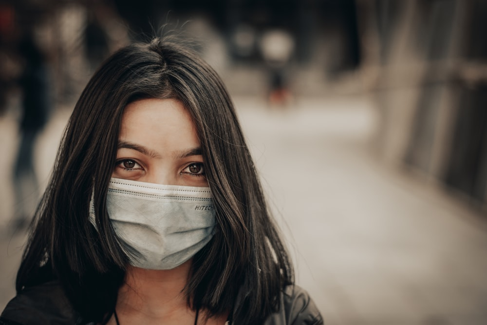 woman in black and white shirt covering face with white face mask