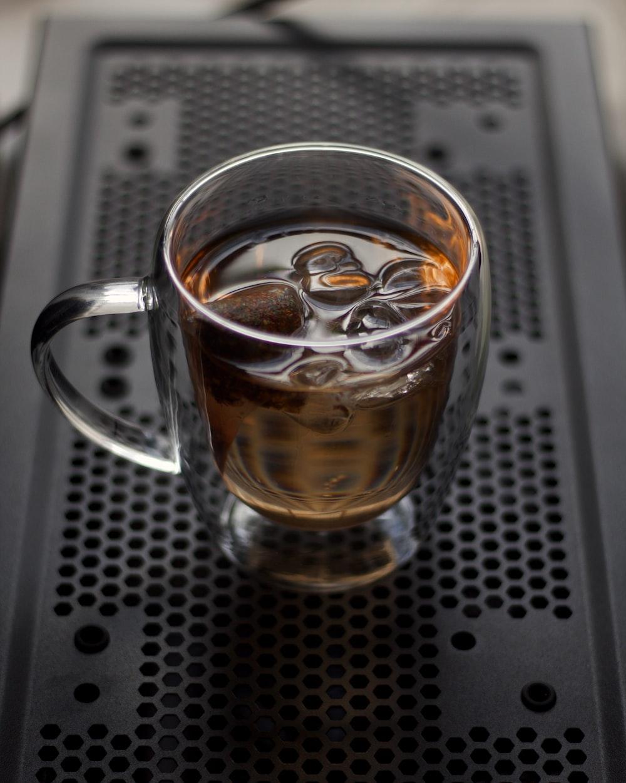 clear glass mug on gray metal table