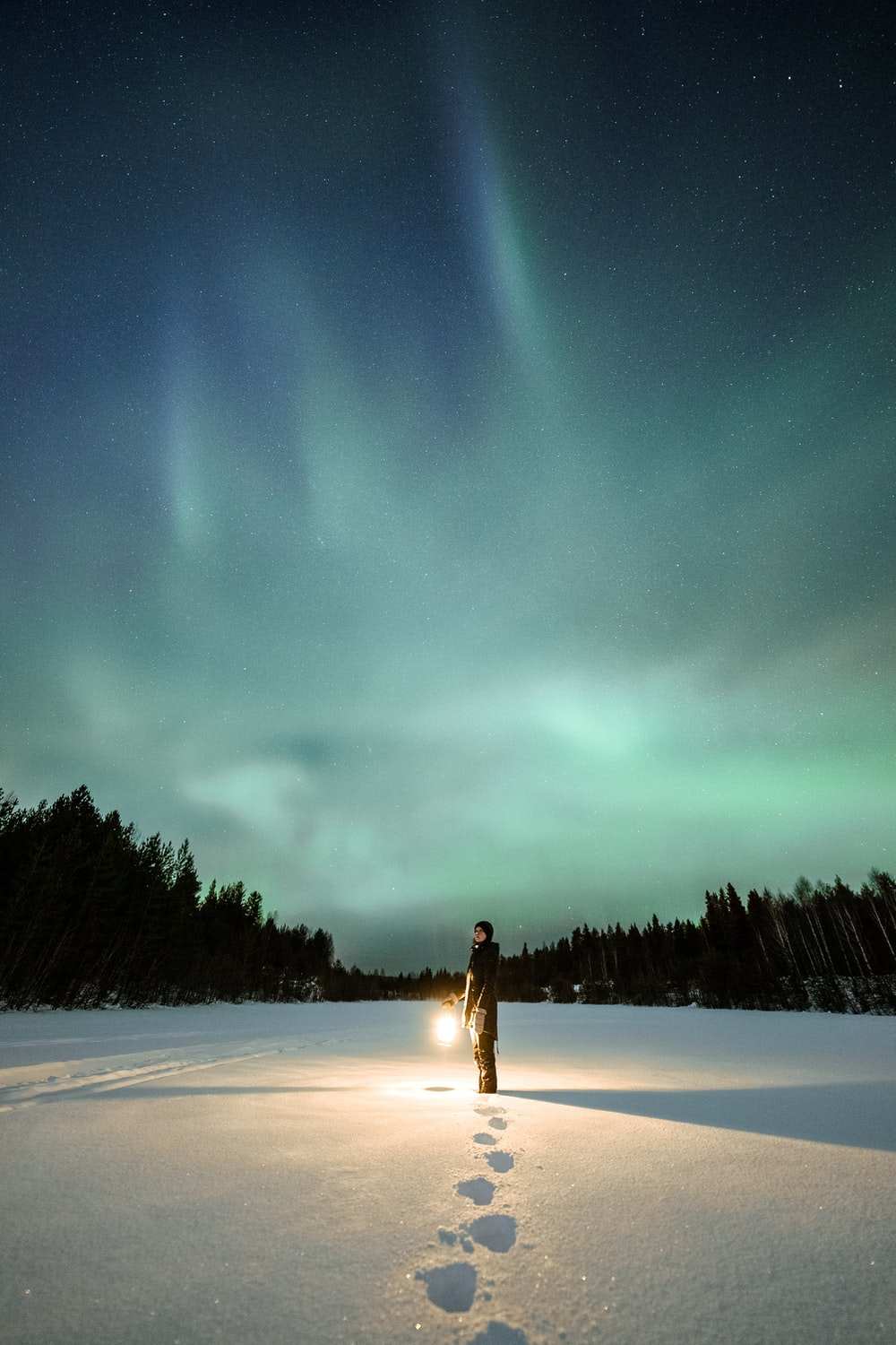 woman in white dress standing on snow covered ground during night time
