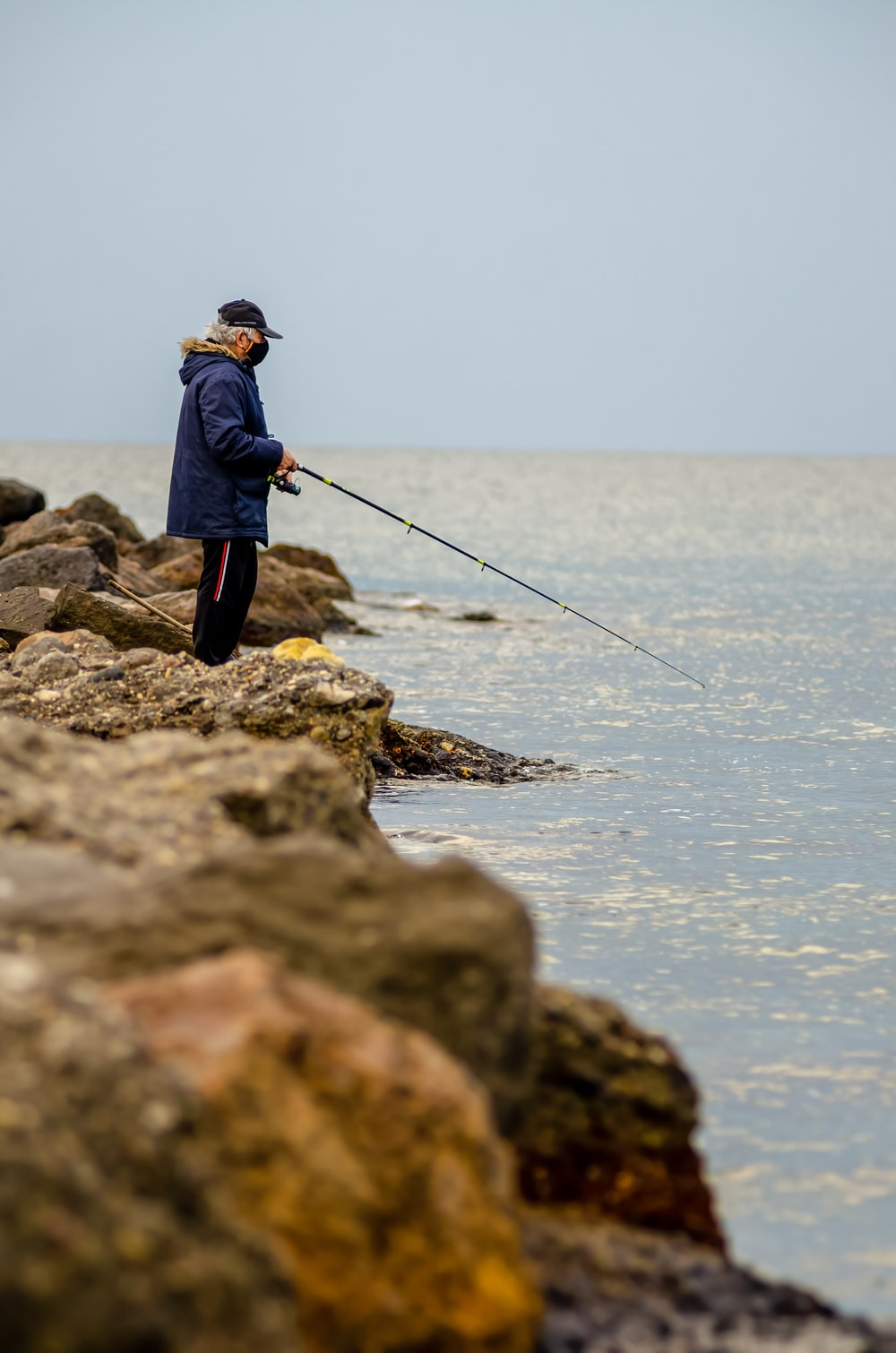 man in blue jacket and black pants fishing on sea during daytime