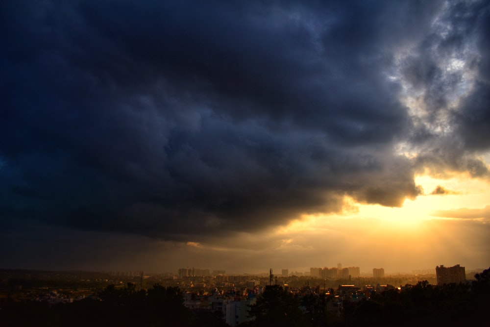 city skyline under gray clouds during sunset