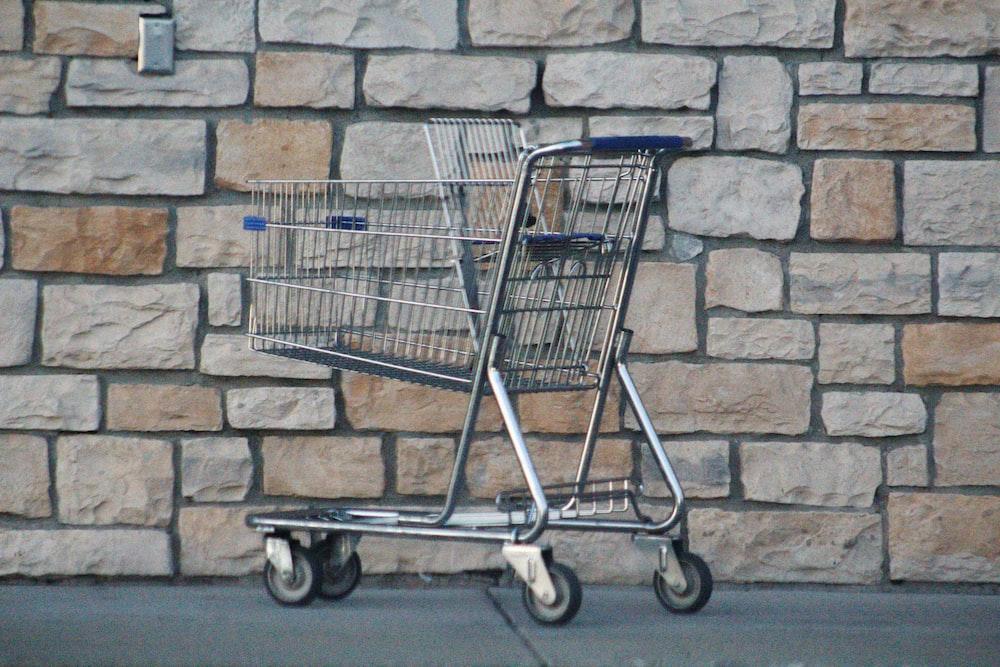 gray shopping cart on gray brick wall