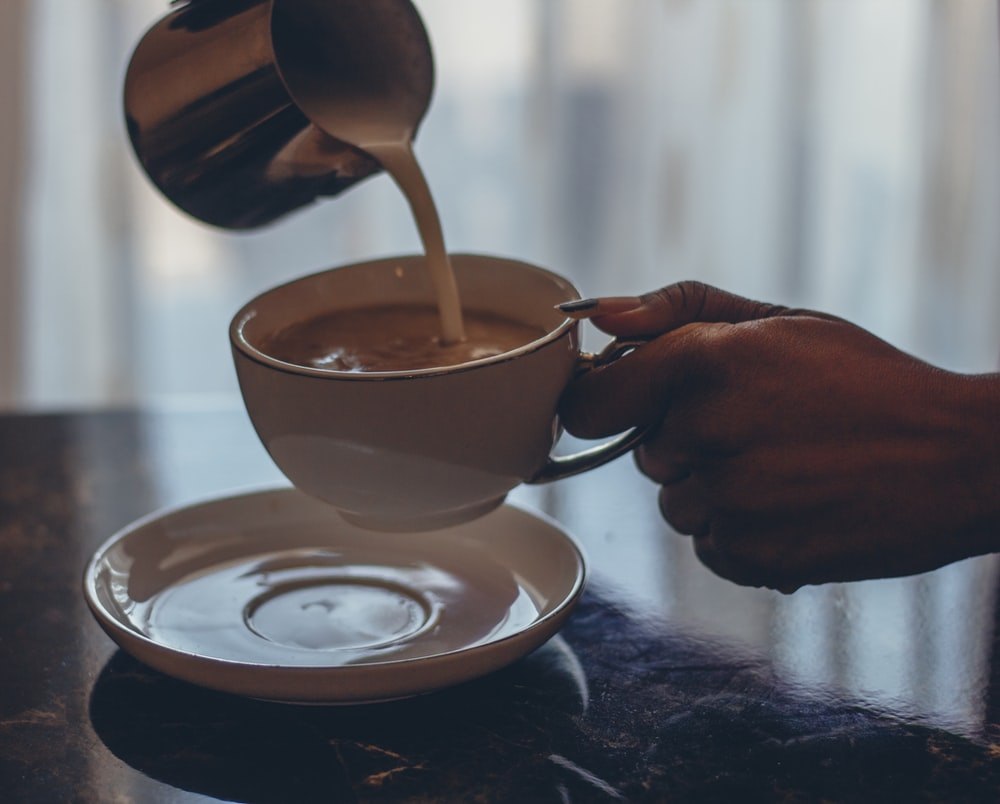 person holding white ceramic mug with brown wooden spoon