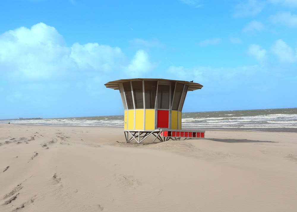 yellow and white lifeguard tower on beach during daytime