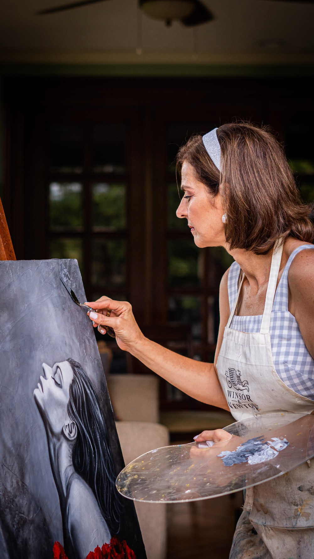 woman in white tank top holding black board