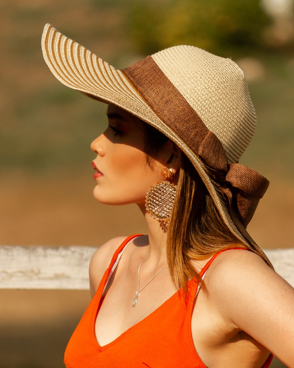 woman in brown and white sun hat and orange tank top