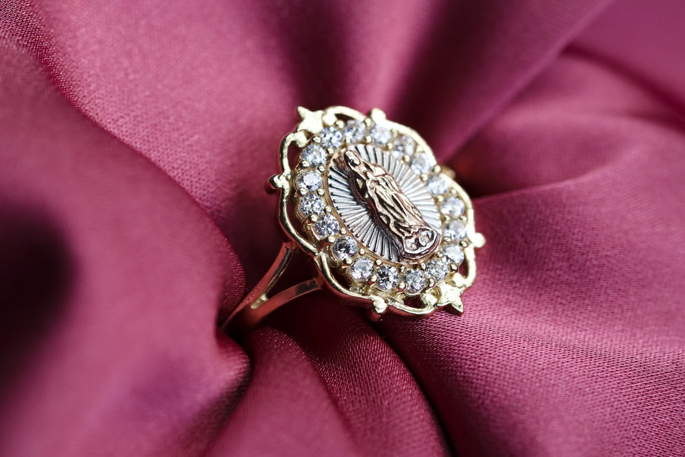 silver diamond studded ring on pink textile