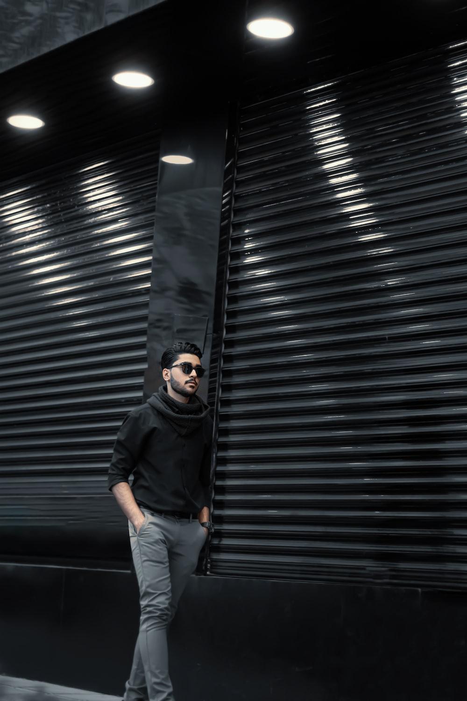 man in black jacket and blue denim jeans standing beside roll up door