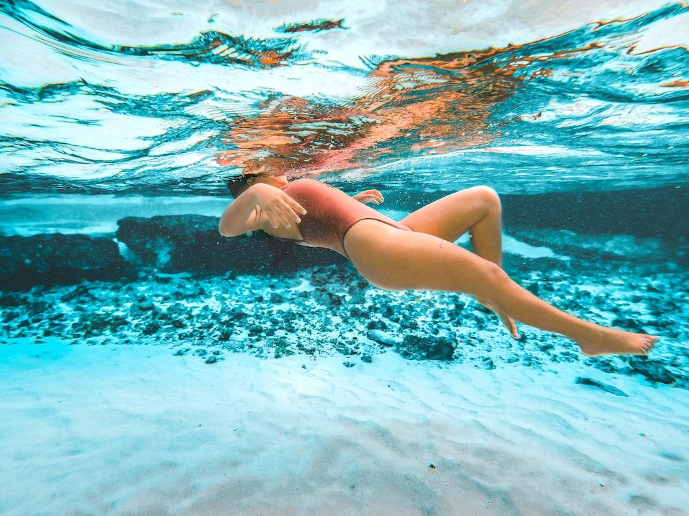woman in blue bikini bottom swimming in water