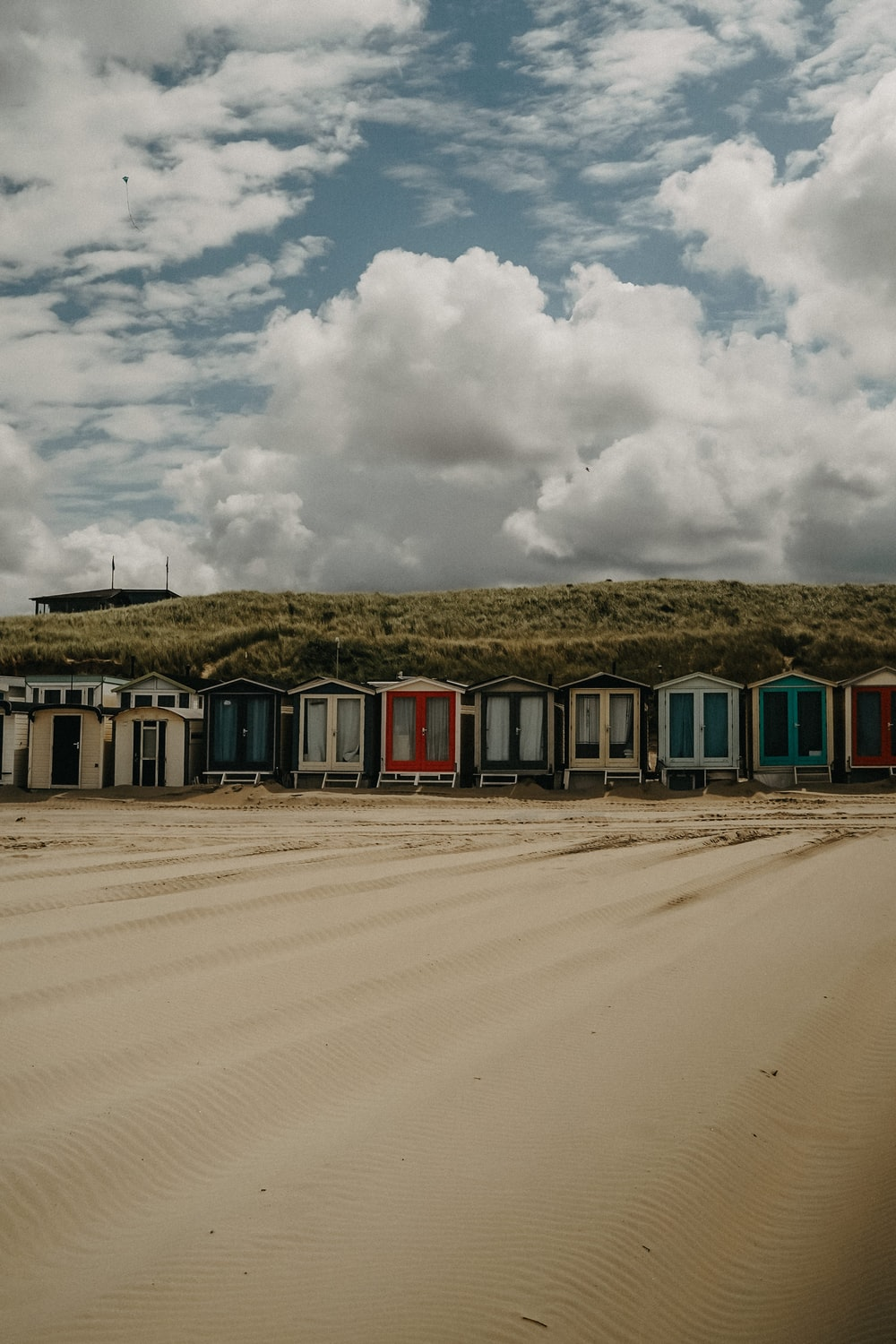 red and white wooden house on brown sand under white clouds during daytime