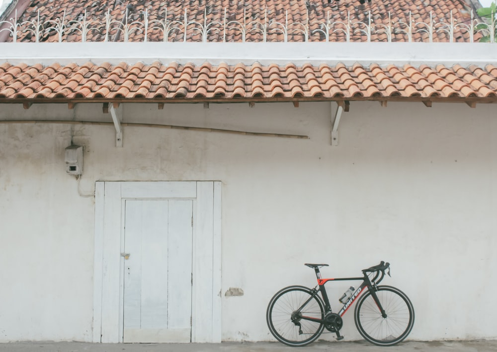 red and black mountain bike parked beside white wooden door