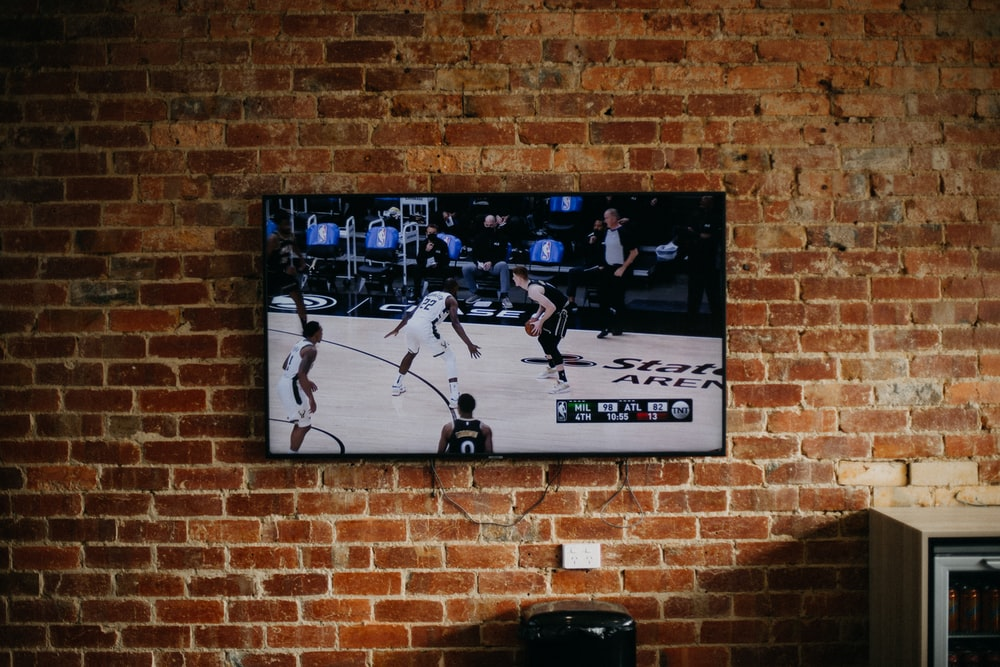 black flat screen tv mounted on brown brick wall