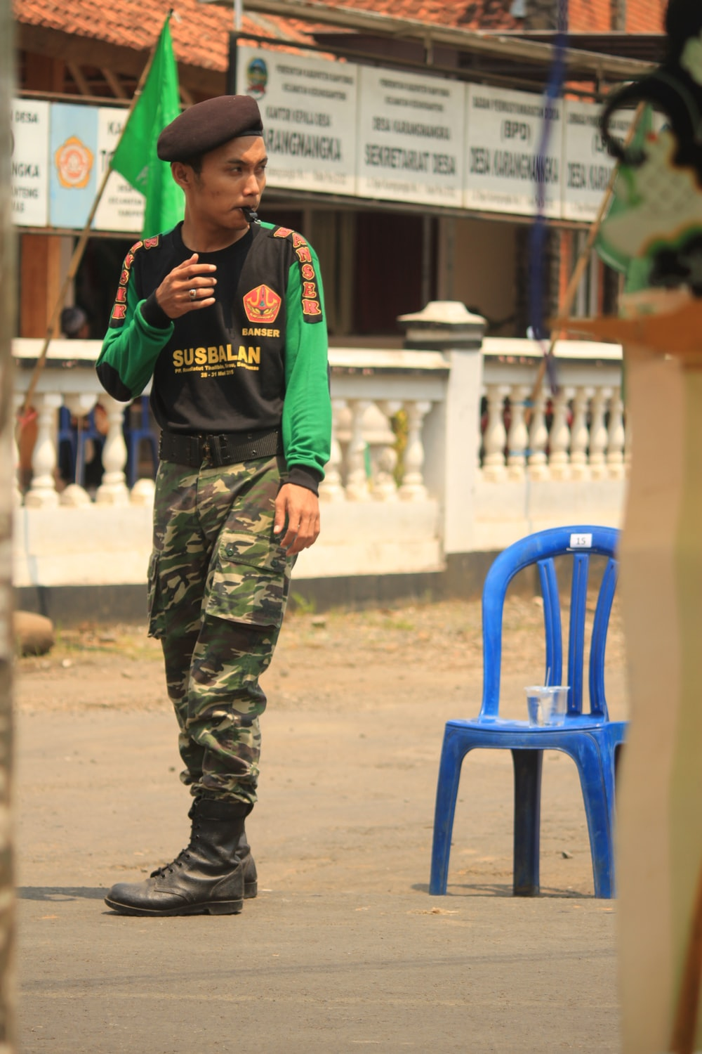 man in green and black camouflage pants and blue shirt holding a phone