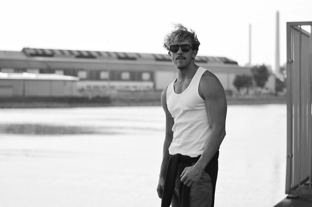 man in white tank top and black pants wearing sunglasses standing on white sand during daytime