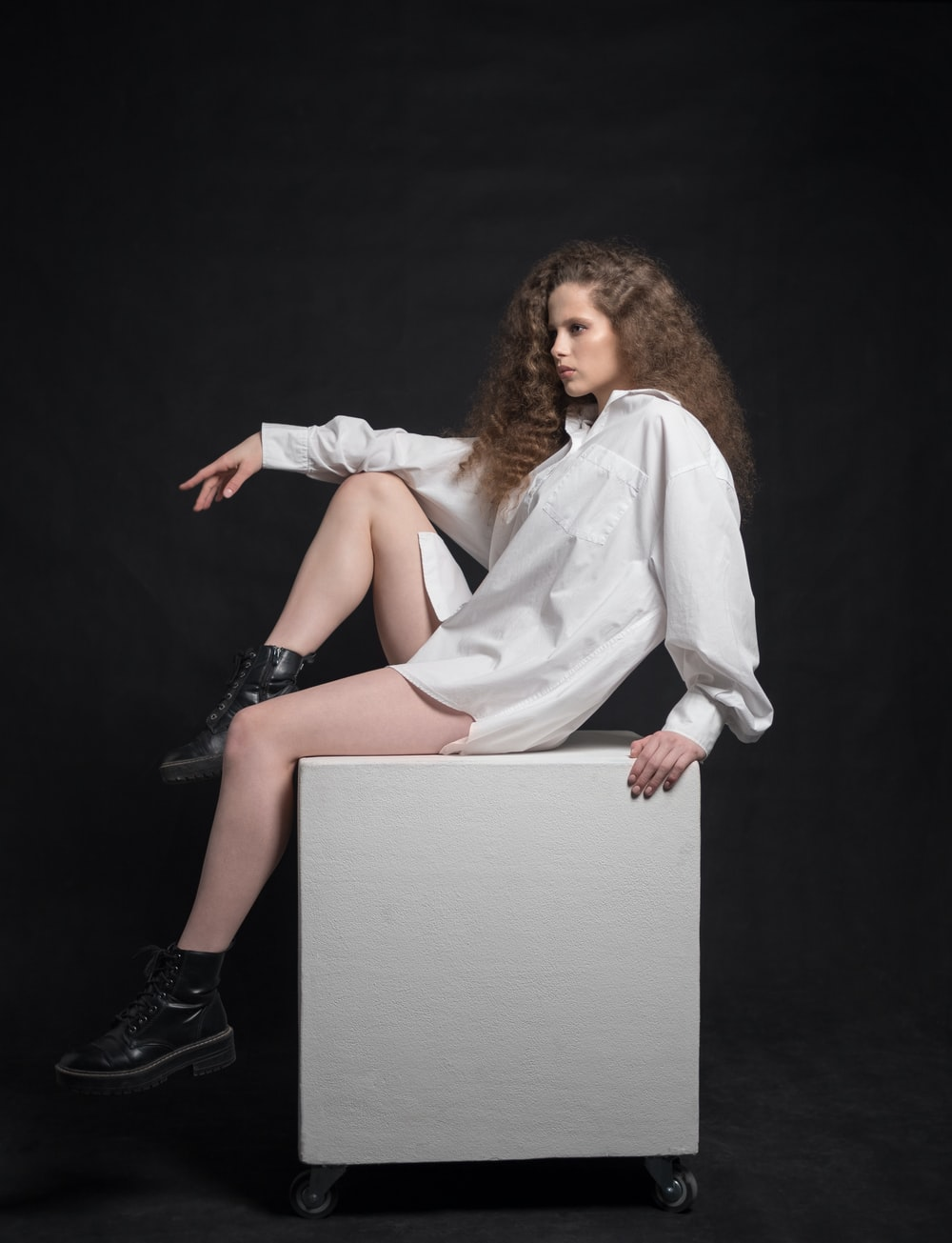 woman in white long sleeve shirt and black skirt sitting on white wooden table
