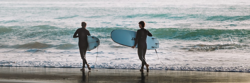 man and woman holding white surfboard walking on beach during daytime