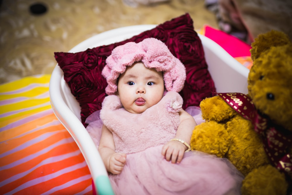 baby in pink dress lying on white and red striped bed