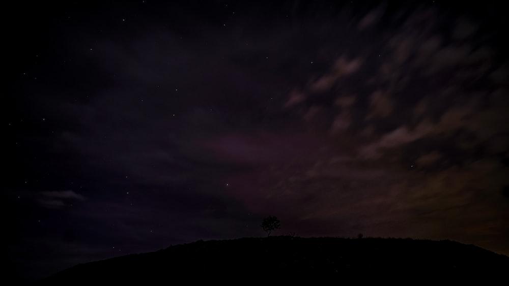 silhouette of mountain under dark sky
