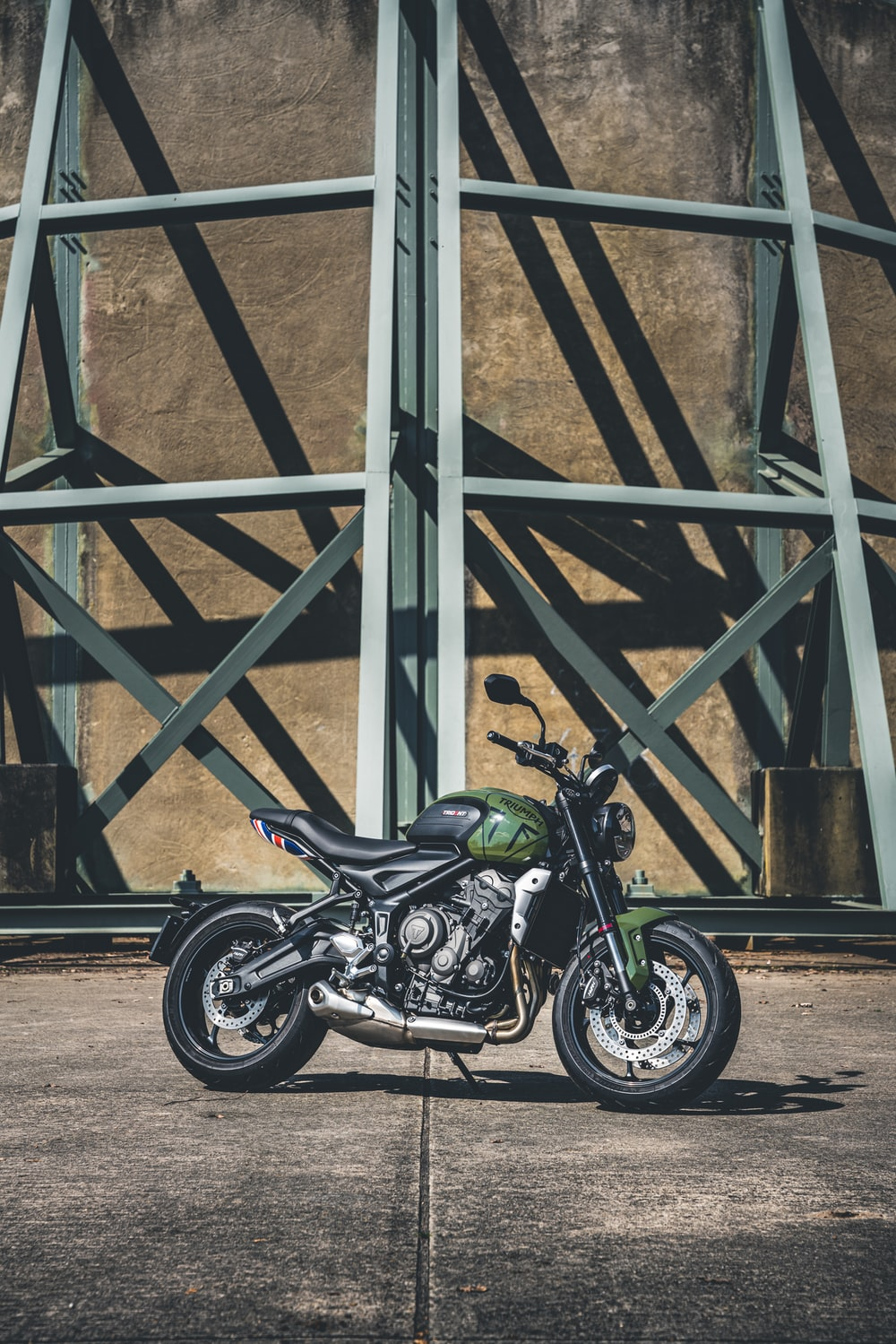 black and green sports bike parked beside gray metal frame