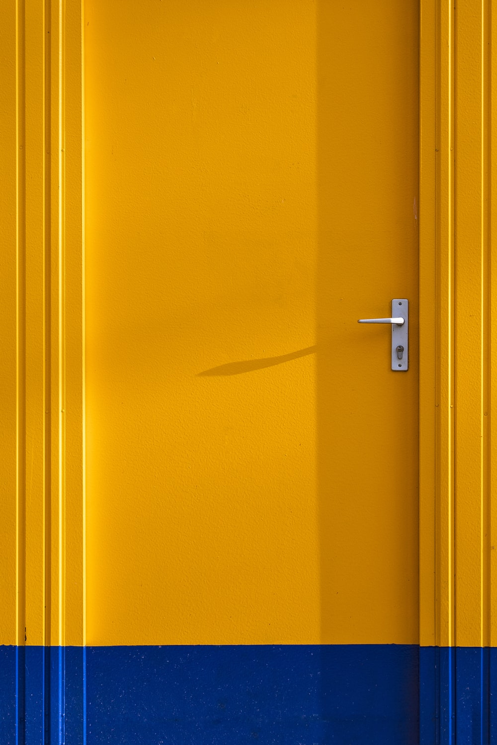 yellow wooden door with silver door lever