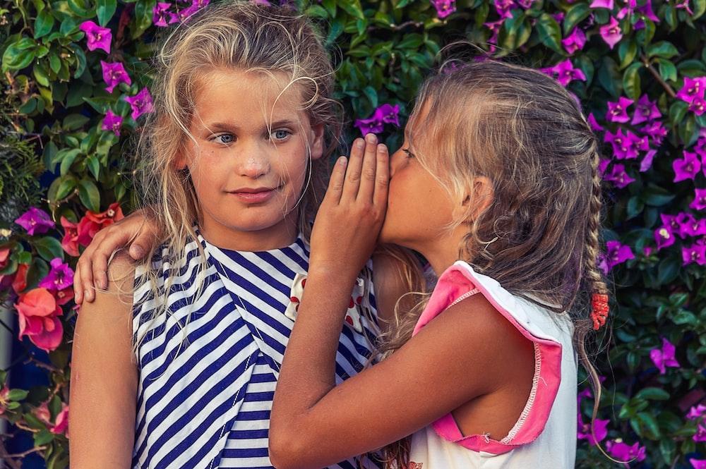 girl in white shirt kissing girl in blue and white stripe shirt
