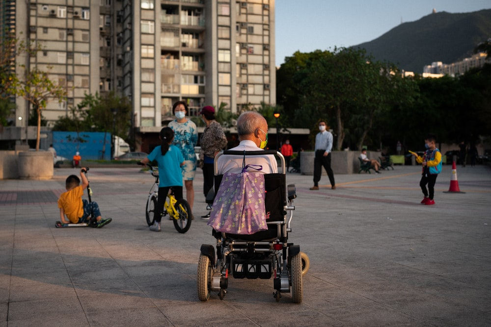woman in pink shirt riding on black and red wheel chair