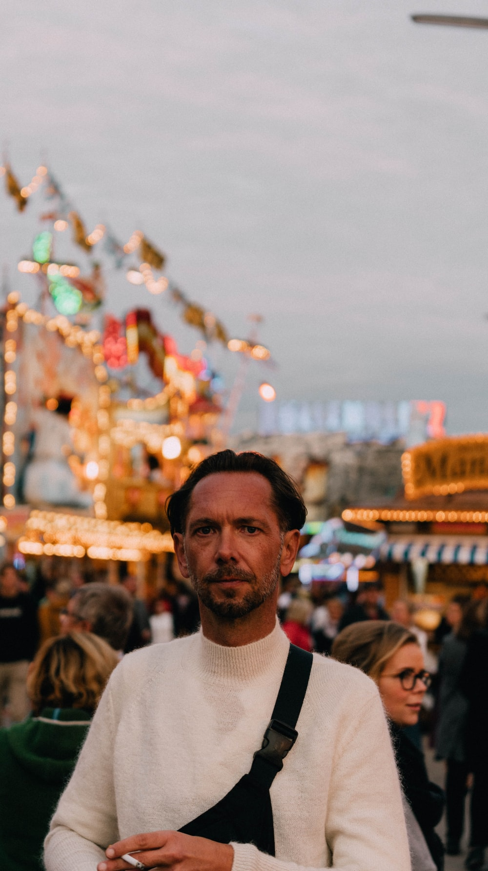 man in white crew neck shirt standing near people during daytime