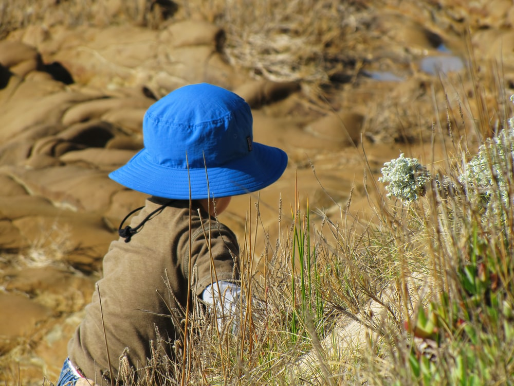 person wearing blue hat and brown pants