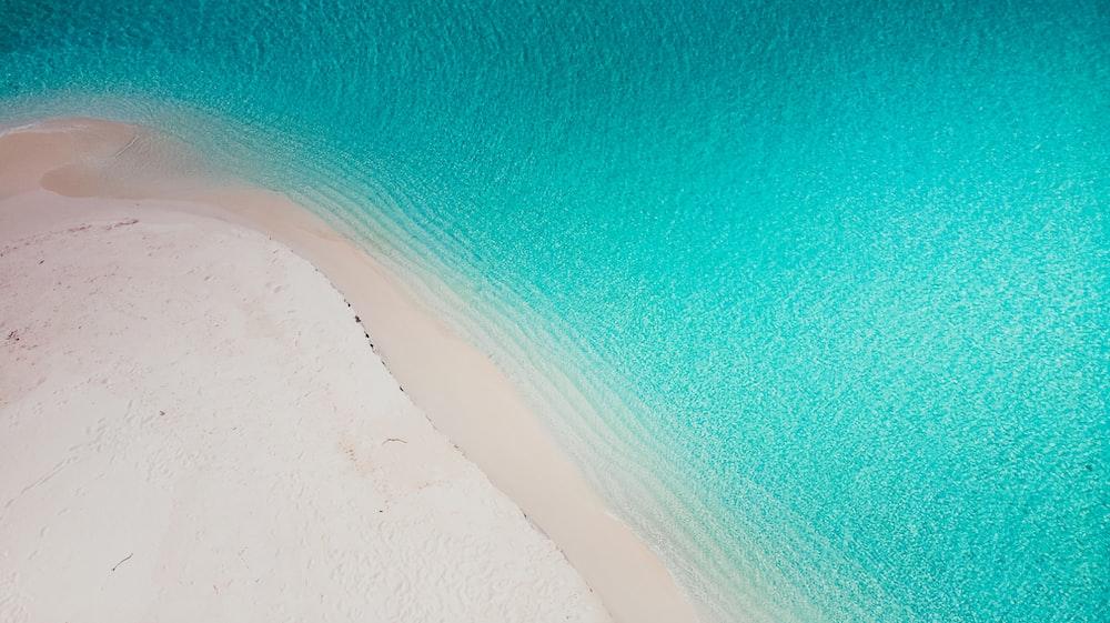 white sand beside blue water