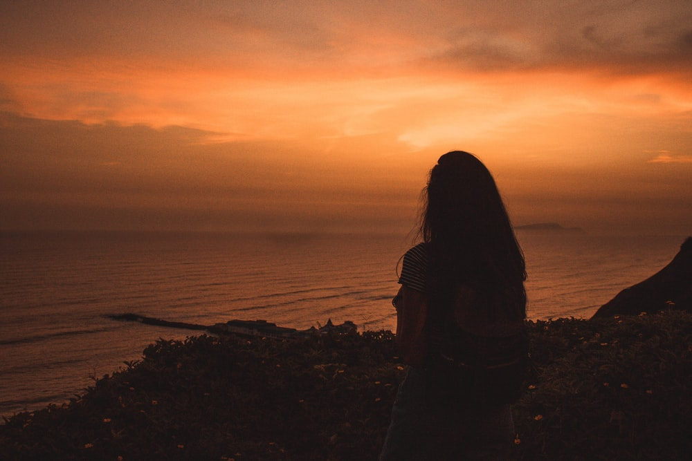 silhouette of woman standing near body of water during sunset