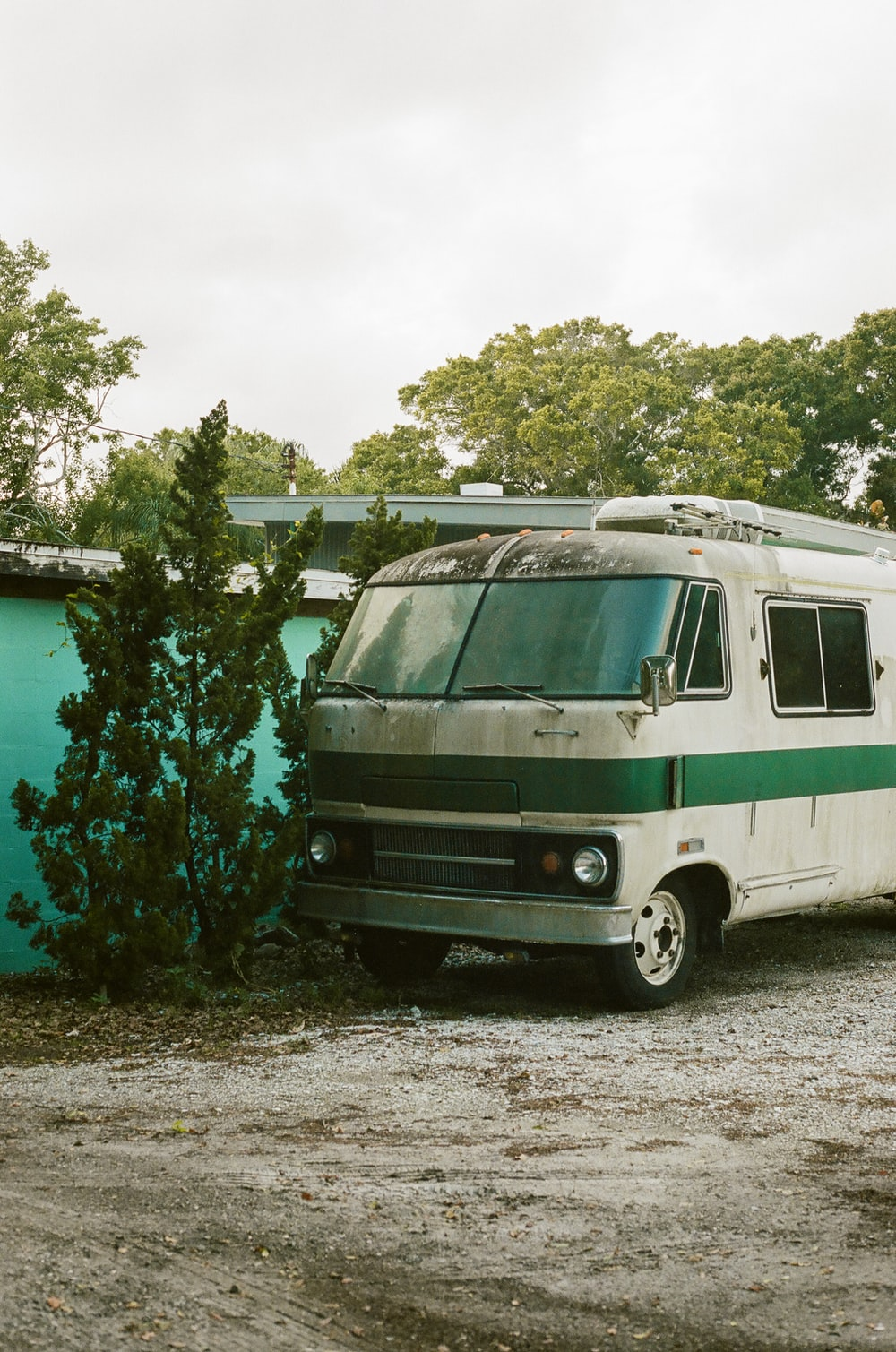 white and green rv trailer parked beside green trees during daytime