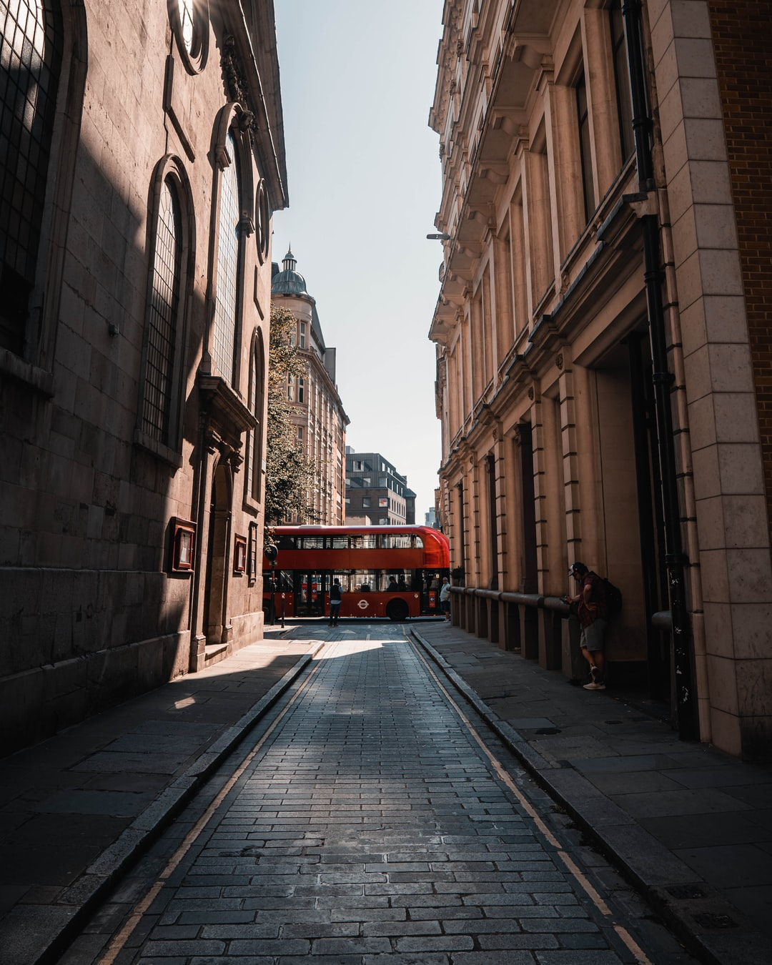 red bus in between of brown concrete buildings during daytime