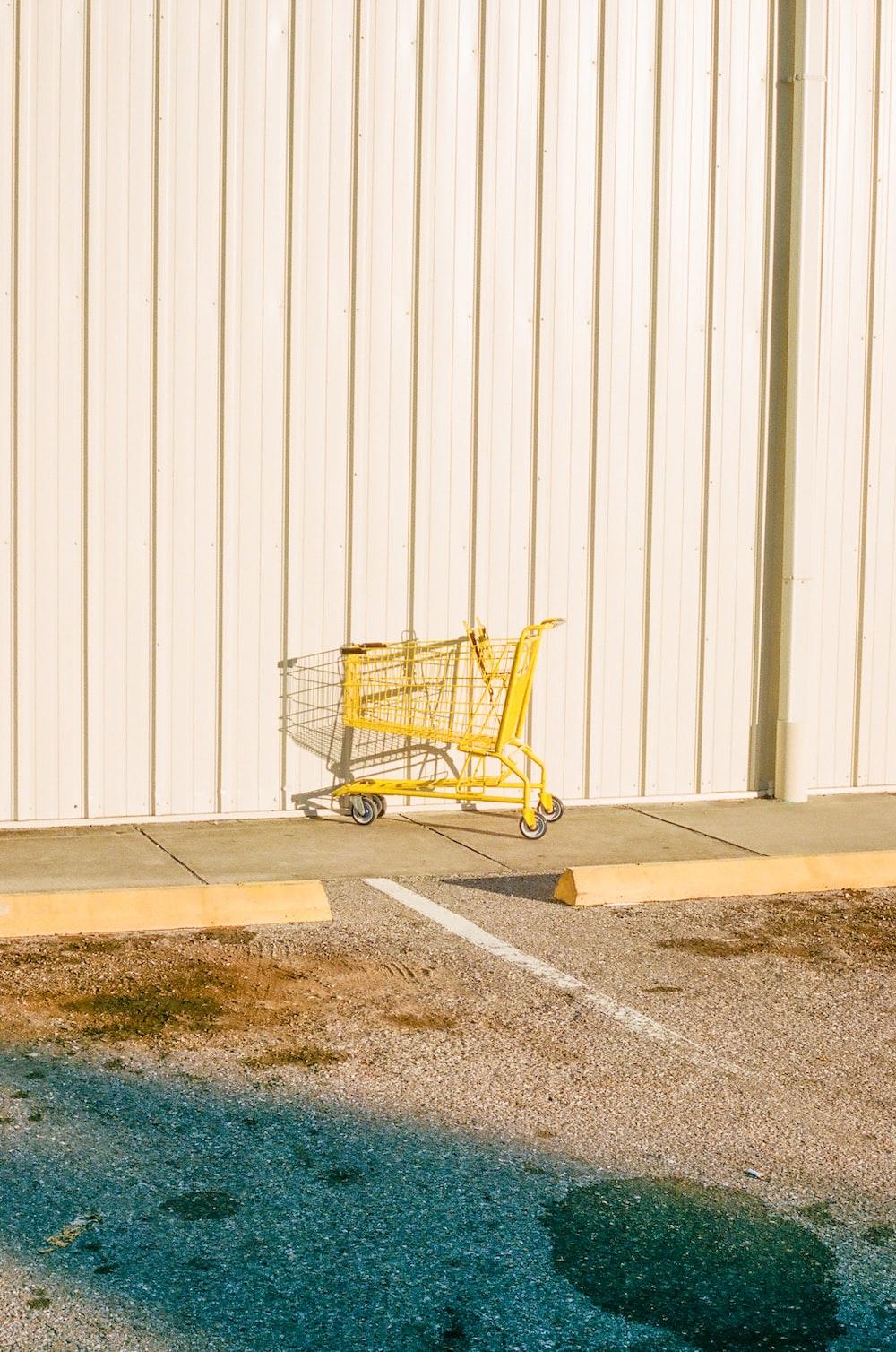 yellow shopping cart on gray concrete floor