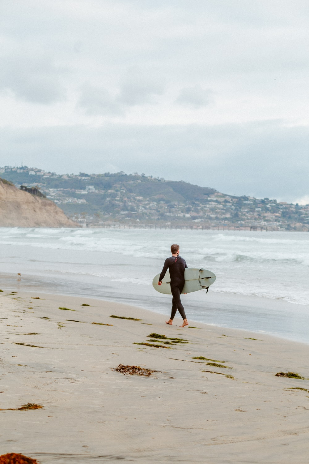 man in black shorts carrying white surfboard walking on beach during daytime
