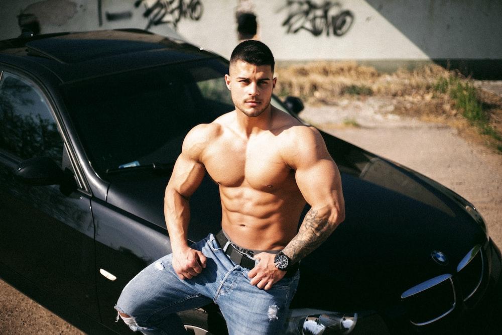 topless man in blue denim jeans sitting on car hood