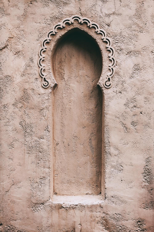brown metal chain on white concrete wall