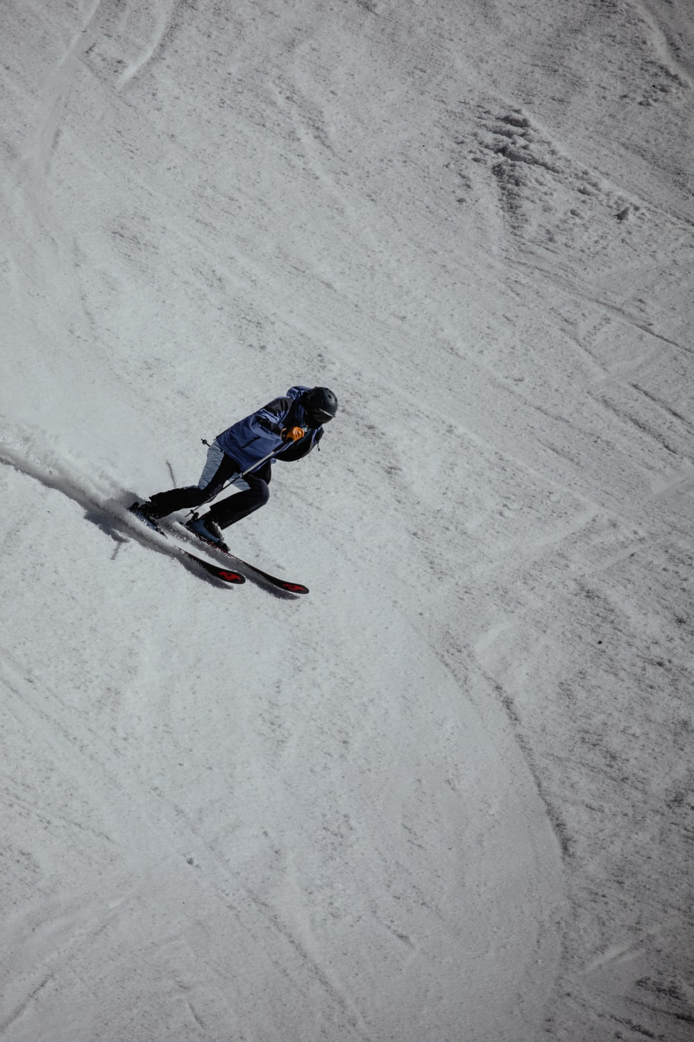 man in blue jacket and black pants riding snowboard on snow covered ground during daytime