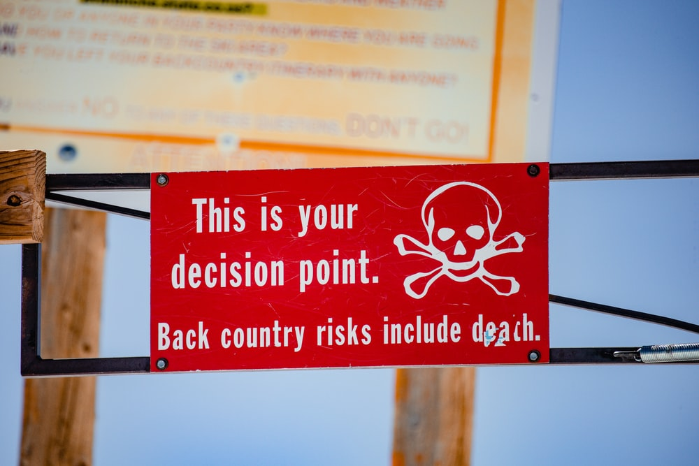 red and white signage on brown wooden post