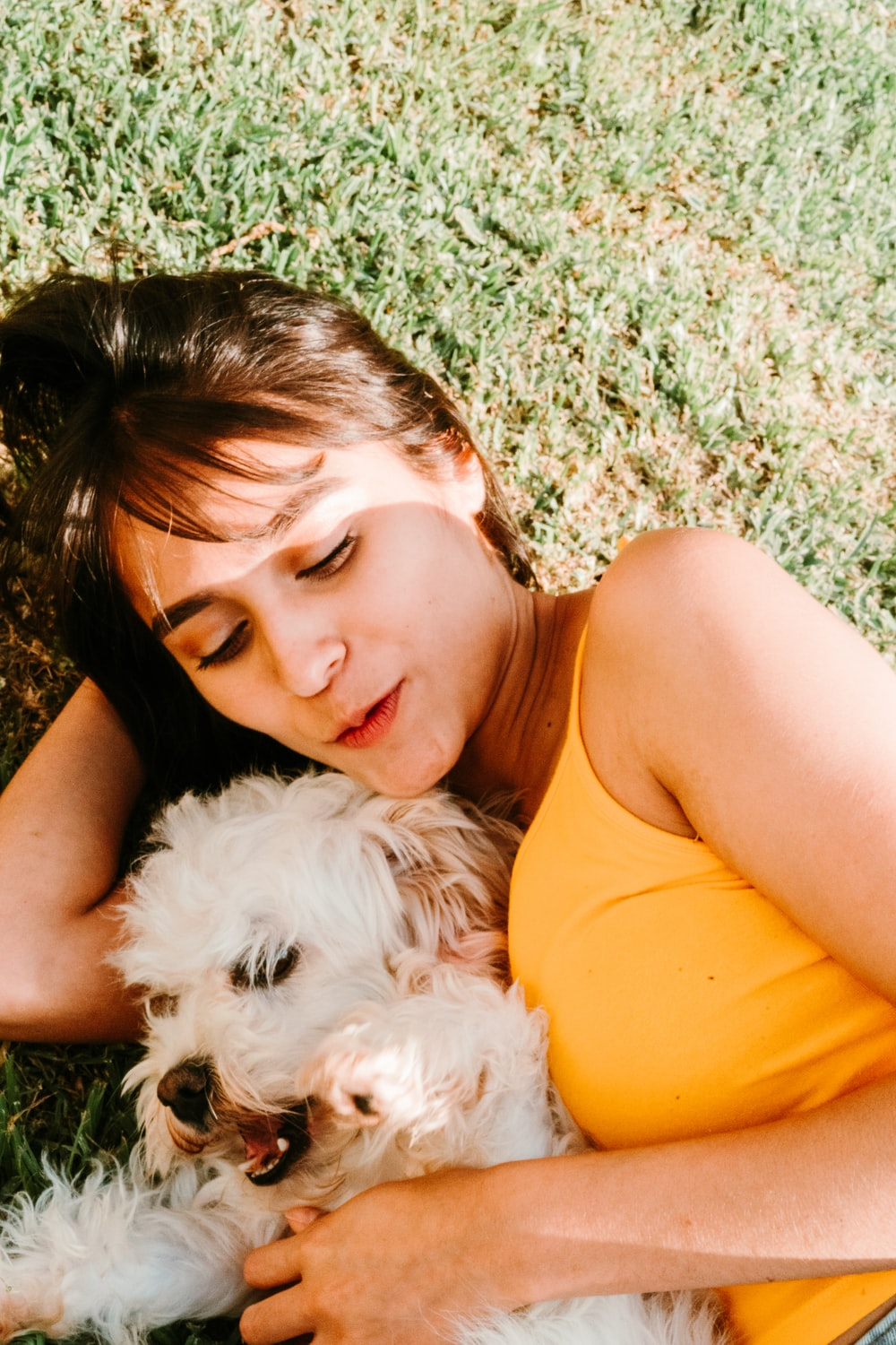 woman in orange tank top lying on green grass field with white long coated small dog