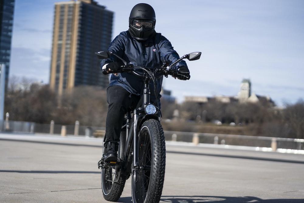 man in black motorcycle helmet riding motorcycle on road during daytime