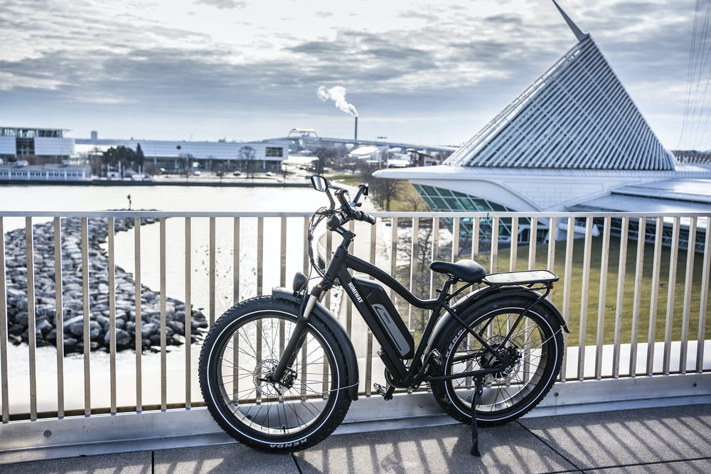 black and gray bicycle beside blue wooden fence during daytime
