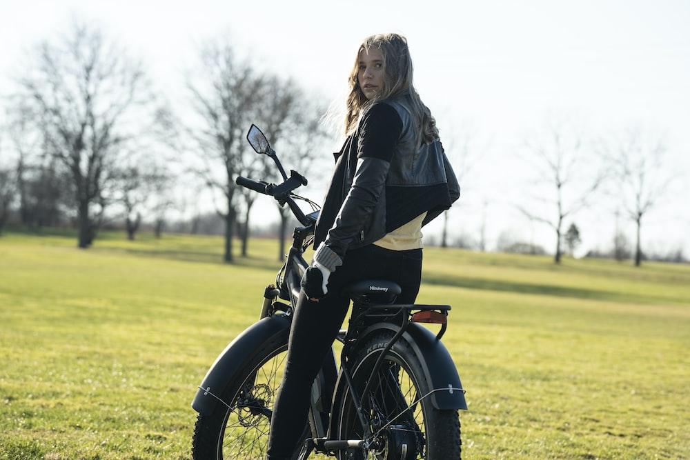 woman in black jacket riding on black motorcycle during daytime