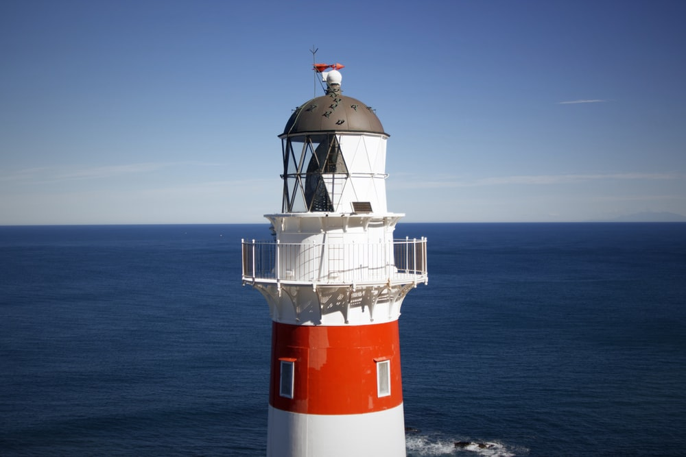 white and red lighthouse on the sea during daytime