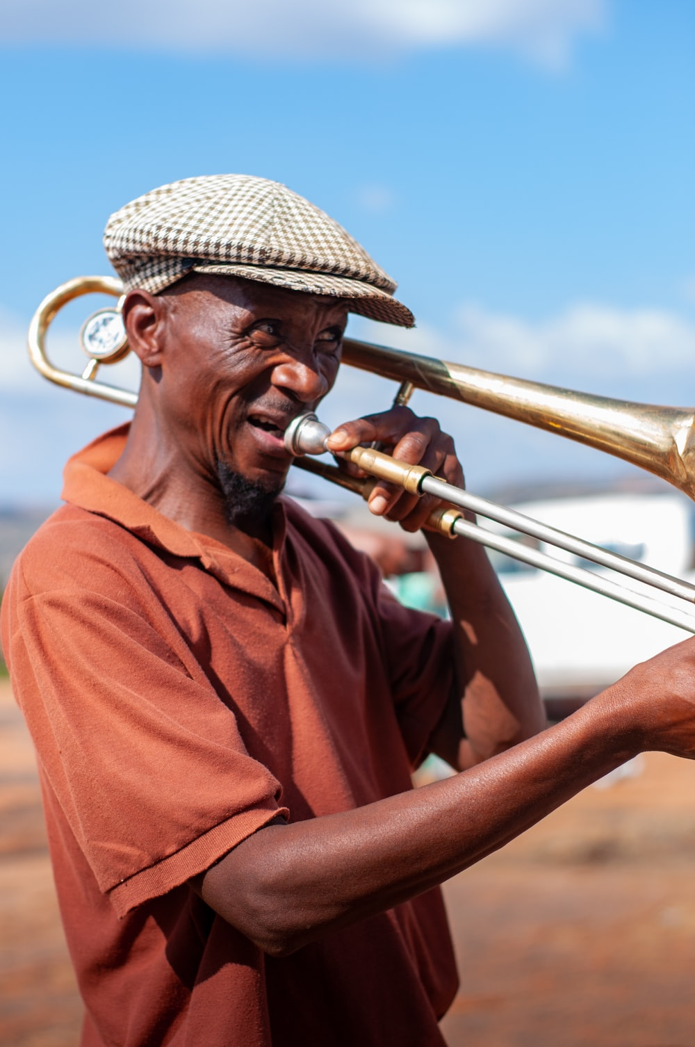 man in red polo shirt wearing brown hat holding brass trumpet during daytime