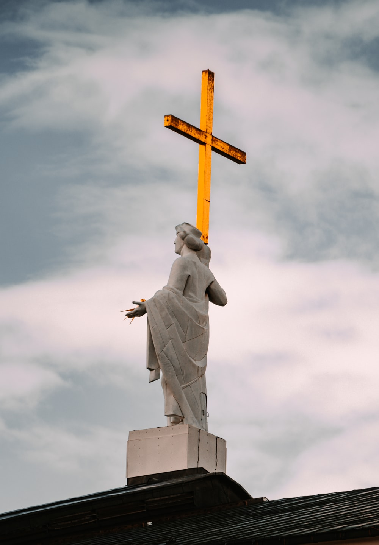 man in robe holding cross statue
