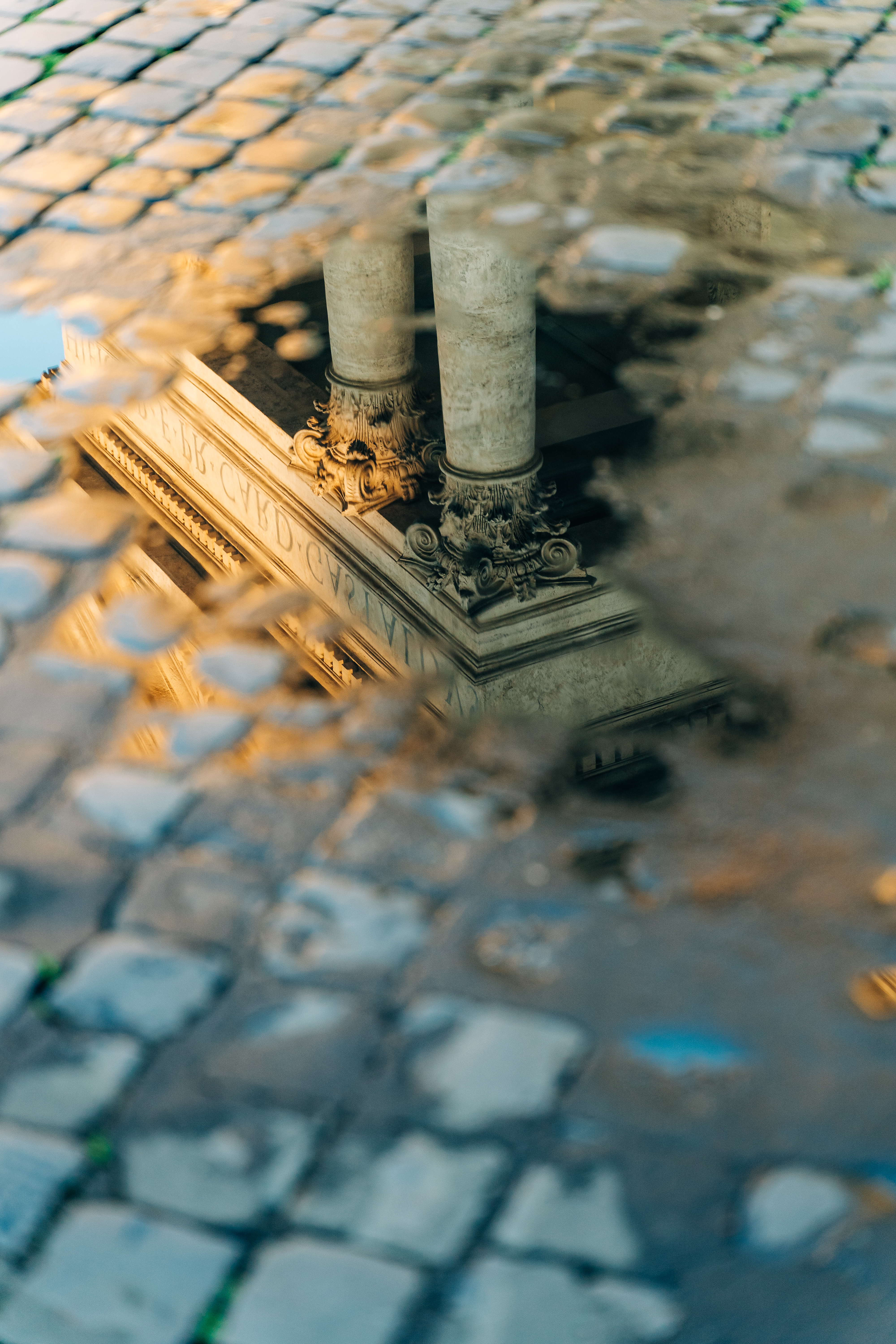 Antique columns reflected in a puddle in Rome, Italy