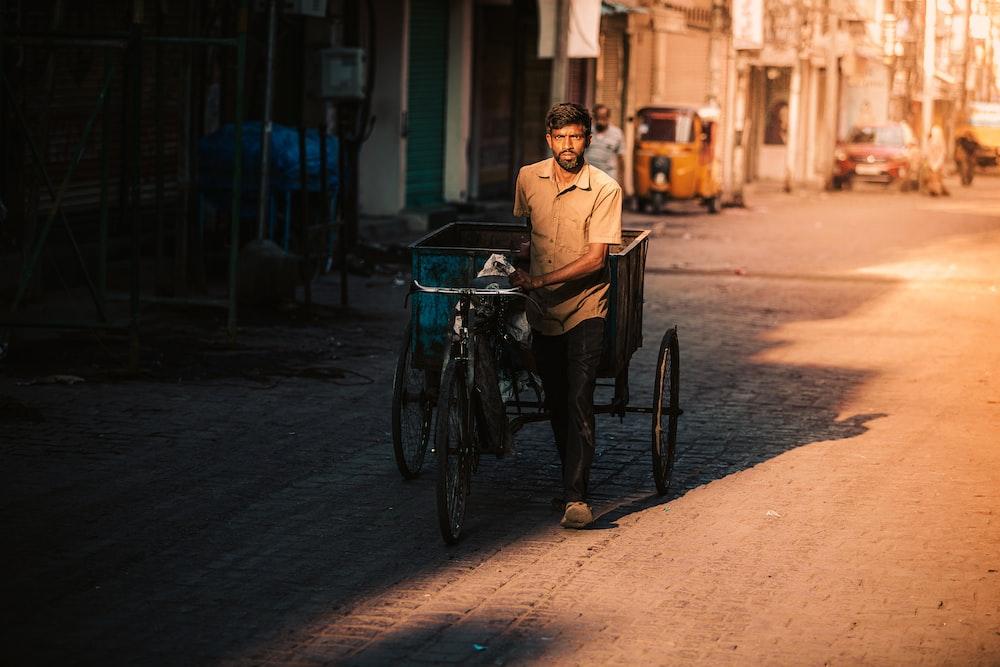 man in brown dress shirt riding on bicycle during daytime